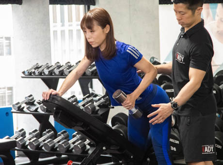 無理に運動している女性とトレーナー